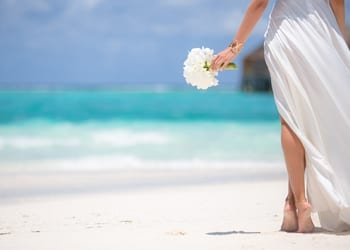 A bride walking barefoot on the sand whilst carrying a small bouquet of flowers