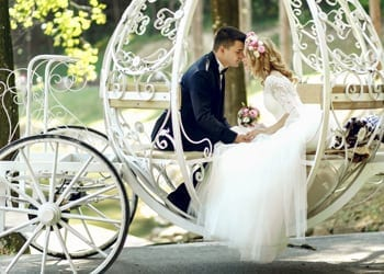A couple sit inside a white horse-drawn carriage during their wedding