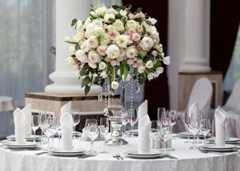 Formal wedding reception complete with floral arrangement and folded napkins