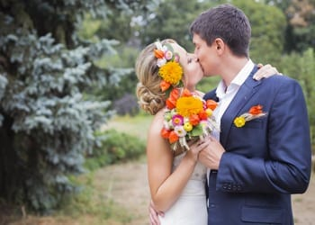 A bride and groom kissing at their outdoor wedding