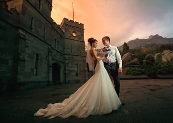 A bride and groom posing in front of a castle during sunset