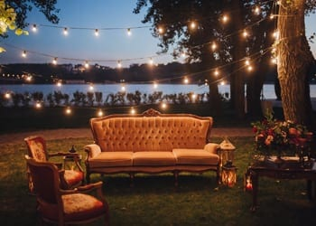 Luxurious antique furniture underneath hanging lights during a night time wedding celebration