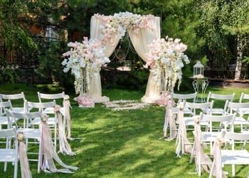 An outdoor wedding arch decorated with floral arrangements and luxurious drapes.
