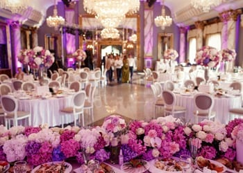 Purple floral arrangements and lighting at a wedding reception