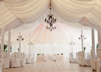 View of a main ballroom area underneath a large wedding tent