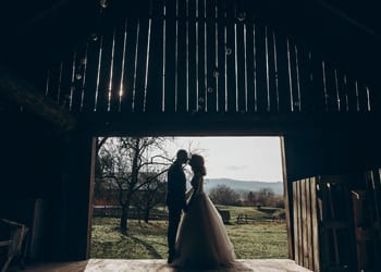A bride and groom kissing under the archway of a barnyard door