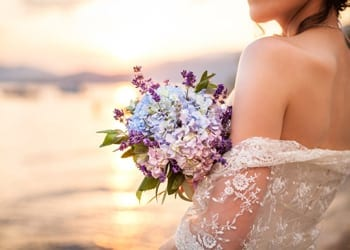 A bride holding a bouquet during as summertime wedding
