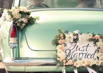 A vintage bridal car with a just married sign on the back