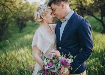 A happy bride and groom looking radiant in vintage style wedding day outfits
